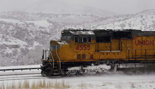 A Union Pacific freight train kicks up snow as it barrels down the tracks along Interstate 70 west of Glenwood Springs Monday.