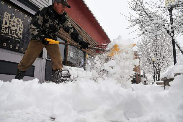 Snow flies as Roger Grove of New Castle clears off around five inches of fresh snow from the sidewalk in front of his resturant Monday.