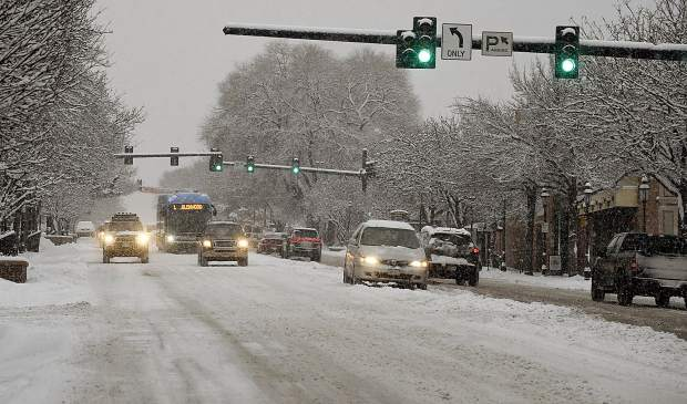 Christmas Eve traffic navigates a snow-covered Grand Avenue Monday in Glenwood Springs.