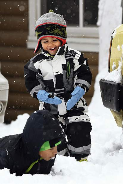 Santiago Sarabia, 2, laughs at his brother Mateo, 10 as he crawls through the snow in their driveway Monday in Silt.