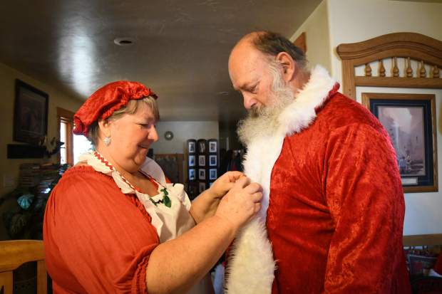 Antonelli's wife Waynetta helps him get ready for a gig as Santa in their home in Silt.