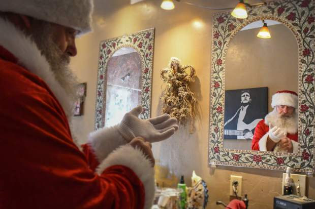 Kim Antonelli makes last minute adjustments before an evening as Santa at a private party.
