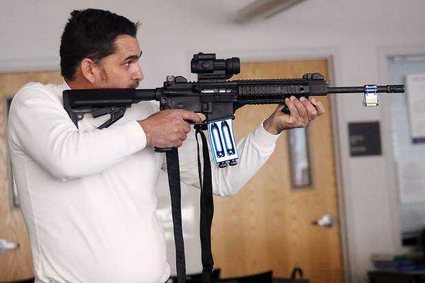 Raul Gudino takes aim during a scenario training exercise at the Basalt Police Department's community police academy on Saturday, Dec. 1, 2018, at Basalt High School. (Photo by Austin Colbert/The Aspen Times).