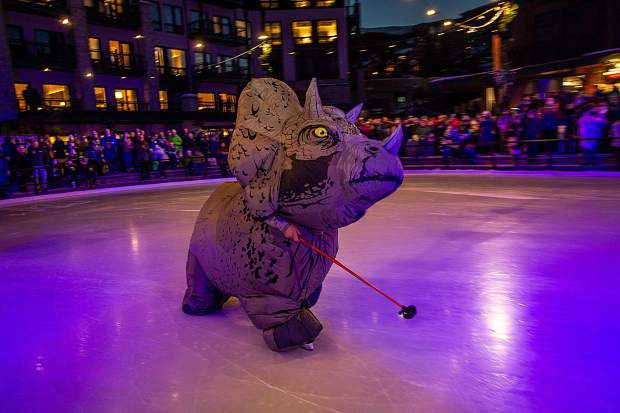 A triceratop dinosaur skates on the new ice rink at the Snowmass Base Village grand opening on Saturday.