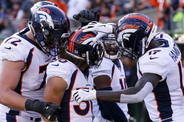 Denver Broncos running back Phillip Lindsay (30) celebrates his touchdown with his teammates in the first half of an NFL football game against the Cincinnati Bengals, Sunday, Dec. 2, 2018, in Cincinnati. (AP Photo/Gary Landers)