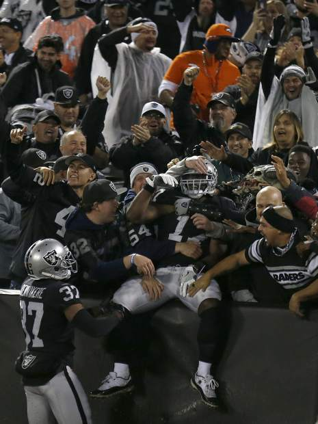 Oakland Raiders' Dwayne Harris, center, celebrates with fans after returning a punt for a touchdown against the Denver Broncos during the first half of an NFL football game in Oakland, Calif., Monday, Dec. 24, 2018. (AP Photo/D. Ross Cameron)