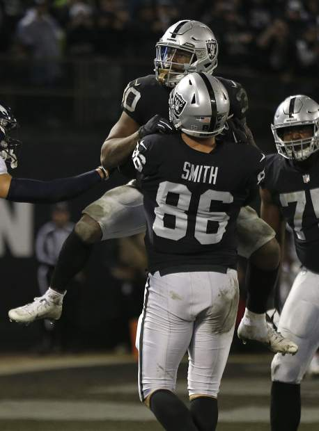 Oakland Raiders running back Jalen Richard, top, celebrates with tight end Lee Smith (86) after scoring against the Denver Broncos during the second half of an NFL football game in Oakland, Calif., Monday, Dec. 24, 2018. (AP Photo/D. Ross Cameron)