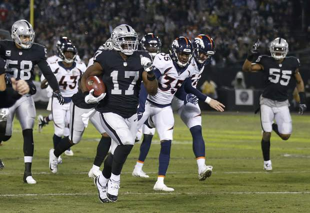 Oakland Raiders' Dwayne Harris (17) returns a punt for a touchdown against the Denver Broncos during the first half of an NFL football game in Oakland, Calif., Monday, Dec. 24, 2018. (AP Photo/D. Ross Cameron)