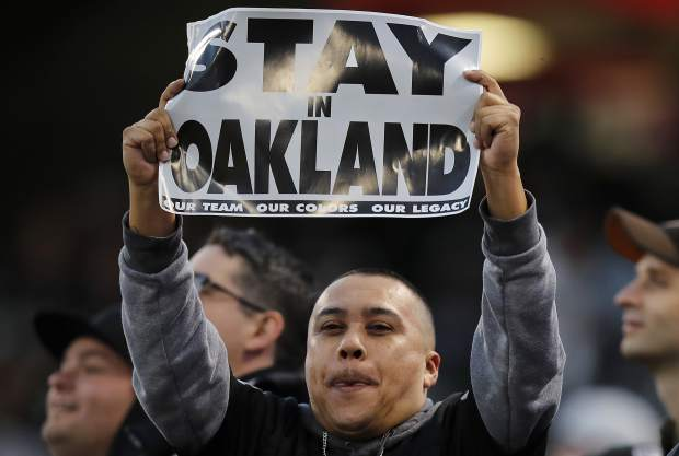 An Oakland Raiders fan holds up a sign before an NFL football game between the Raiders and the Denver Broncos in Oakland, Calif., Monday, Dec. 24, 2018. (AP Photo/John Hefti)