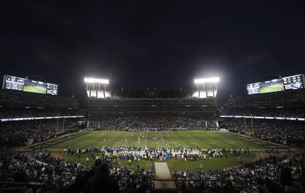 Fans watch the opening kickoff from a general view of Oakland Alameda County Coliseum during the first half of an NFL football game between the Oakland Raiders and the Denver Broncos in Oakland, Calif., Monday, Dec. 24, 2018. (AP Photo/Jeff Chiu)