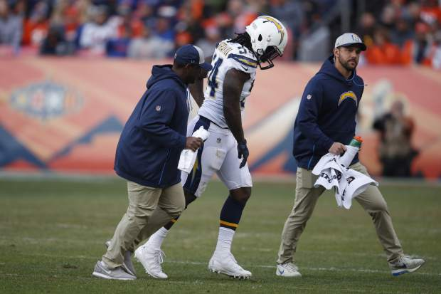 Los Angeles Chargers defensive end Melvin Ingram walks off the field with trainers after an injury during the first half of an NFL football game, Sunday, Dec. 30, 2018, in Denver. (AP Photo/David Zalubowski)