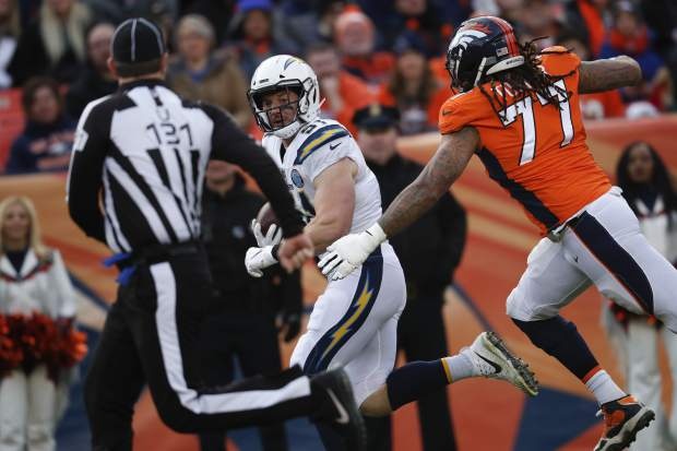 Los Angeles Chargers outside linebacker Kyle Emanuel picks up a fumble on his way to scoring a touchdown during the first half of an NFL football game against the Denver Broncos, Sunday, Dec. 30, 2018, in Denver. (AP Photo/David Zalubowski)