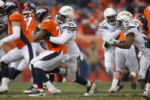 Los Angeles Chargers defensive end Isaac Rochell (98) wraps up Denver Broncos running back Royce Freeman during the first half of an NFL football game, Sunday, Dec. 30, 2018, in Denver. (AP Photo/David Zalubowski)