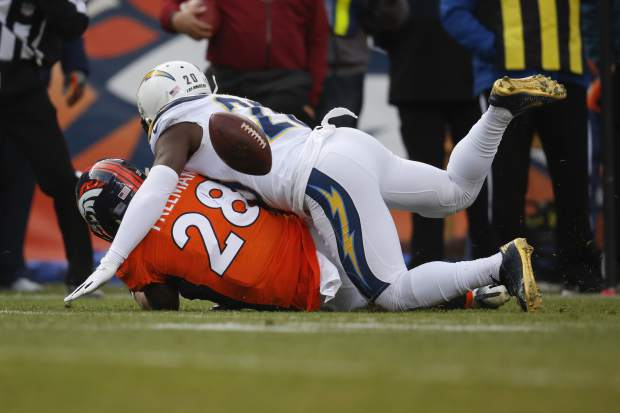 Denver Broncos running back Royce Freeman (28) fumbles the ball as he is hit by the Los Angeles Chargers Desmond King during the first half of an NFL football game, Sunday, Dec. 30, 2018, in Denver. (AP Photo/David Zalubowski)