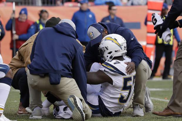 Los Angeles Chargers outside linebacker Jatavis Brown is helped by trainers after an injury during the first half of an NFL football game against the Denver Broncos, Sunday, Dec. 30, 2018, in Denver. (AP Photo/Jack Dempsey)