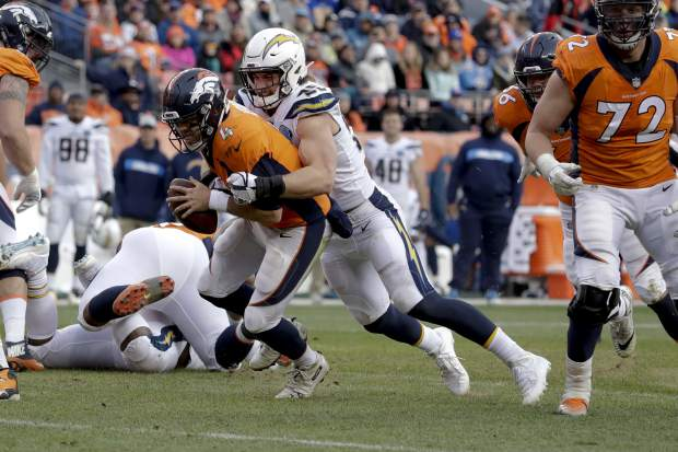Denver Broncos quarterback Case Keenum is sacked by Los Angeles Chargers defensive end Joey Bosa during the first half of an NFL football game, Sunday, Dec. 30, 2018, in Denver. (AP Photo/Jack Dempsey)