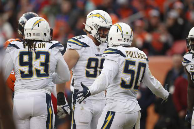 Los Angeles Chargers defensive end Joey Bosa, center, celebrates with teammate linebacker Hayes Pullard (50) after sacking Denver Broncos quarterback Case Keenum during the first half of an NFL football game, Sunday, Dec. 30, 2018, in Denver. (AP Photo/David Zalubowski)