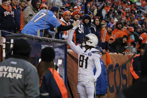 Los Angeles Chargers wide receiver Mike Williams (81) reacts with a fan after scoring a touchdown during the second half of an NFL football game against the Denver Broncos, Sunday, Dec. 30, 2018, in Denver. (AP Photo/Jack Dempsey)