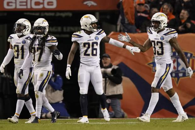 Los Angeles Chargers cornerback Casey Hayward, center, celebrates after running an interception back for a touchdown during the second half of an NFL football game against the Denver Broncos, Sunday, Dec. 30, 2018, in Denver. (AP Photo/Jack Dempsey)