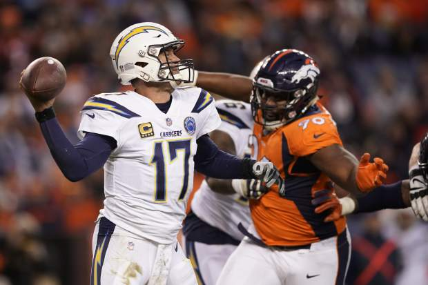 Los Angeles Chargers quarterback Philip Rivers, left throws a pass during the second half of an NFL football game against the Denver Broncos, Sunday, Dec. 30, 2018, in Denver. (AP Photo/Jack Dempsey)