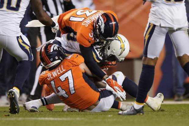 Los Angeles Chargers running back Melvin Gordon, center, is wrapped up by Denver Broncos free safety Justin Simmons (31) and inside linebacker Josey Jewell (47) during the second half of an NFL football game, Sunday, Dec. 30, 2018, in Denver. (AP Photo/Jack Dempsey)
