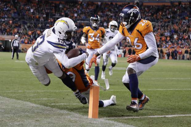 Los Angeles Chargers wide receiver Keenan Allen, left, gets the ball in the end zone for a touchdown as Denver Broncos cornerback Bradley Roby defends during the second half of an NFL football game, Sunday, Dec. 30, 2018, in Denver. (AP Photo/Jack Dempsey)