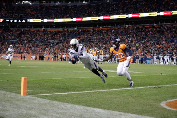 Los Angeles Chargers wide receiver Keenan Allen (13) makes a leaping catch just outside of the end zone as Denver Broncos defensive back Tramaine Brock (22) defends during the second half of an NFL football game, Sunday, Dec. 30, 2018, in Denver. (AP Photo/Jack Dempsey)