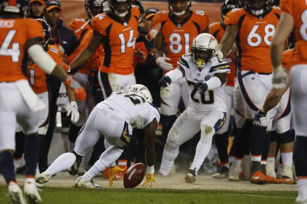 Los Angeles Chargers defensive back Brandon Facyson, center, recovers a fumble during the second half of an NFL football game against the Denver Broncos, Sunday, Dec. 30, 2018, in Denver. (AP Photo/David Zalubowski)