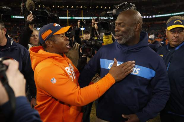 Denver Broncos head coach Vance Joseph, left, greets Los Angeles Chargers head coach Anthony Lynn after an NFL football game, Sunday, Dec. 30, 2018, in Denver. (AP Photo/David Zalubowski)