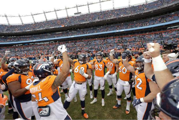 Members of the Denver Broncos react before an NFL football game between the Los Angeles Chargers and the Denver Broncos, Sunday, Dec. 30, 2018, in Denver. (AP Photo/Jack Dempsey)