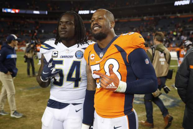 Denver Broncos outside linebacker Von Miller, right, poses with Los Angeles Chargers defensive end Melvin Ingram after an NFL football game, Sunday, Dec. 30, 2018, in Denver. (AP Photo/David Zalubowski)