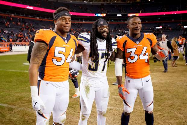 Los Angeles Chargers strong safety Jahleel Addae (37) poses with Denver Broncos strong safety Will Parks (34) and inside linebacker Brandon Marshall (54) after an NFL football game, Sunday, Dec. 30, 2018, in Denver. (AP Photo/Jack Dempsey)