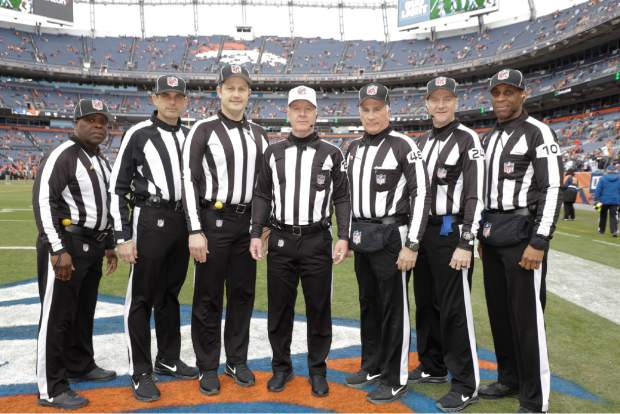 Officials pose before an NFL football game between the Los Angeles Chargers and the Denver Broncos, Sunday, Dec. 30, 2018, in Denver. They are, from right, line judge Julian Mapp (10), down judge David Olive, back judge Perry Paganelli (46), head linesman Patrick Turner (13), umpire Mark Pellis, field judge Matt Edwards, line judge Julien Mapp, and side judge Michael Banks. (AP Photo/Jack Dempsey)