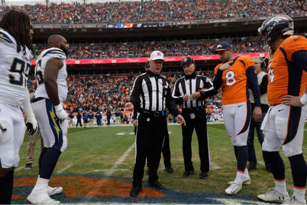 Head linesman Patrick Turner (13) performs the coin toss during the first half of an NFL football game, Sunday, Dec. 30, 2018, in Denver. (AP Photo/Jack Dempsey)