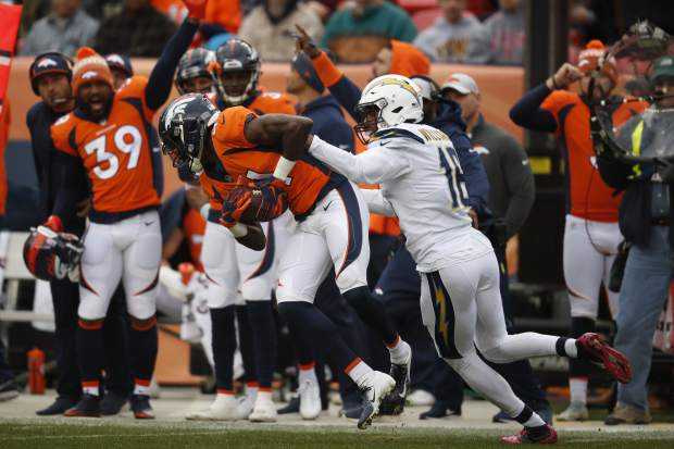 Denver Broncos cornerback Isaac Yiadom intercepts a pass intended for Los Angeles Chargers wide receiver Tyrell Williams, right, during the first half of an NFL football game, Sunday, Dec. 30, 2018, in Denver. (AP Photo/David Zalubowski)