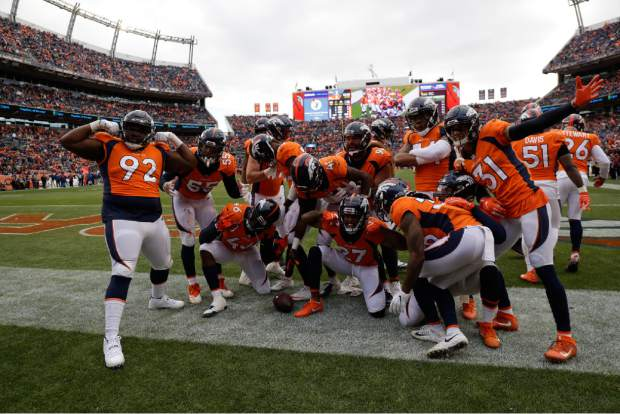 The Denver Broncos defense celebrates after an interception by cornerback Isaac Yiadom during the first half of an NFL football game against the Los Angeles Chargers, Sunday, Dec. 30, 2018, in Denver. (AP Photo/Jack Dempsey)