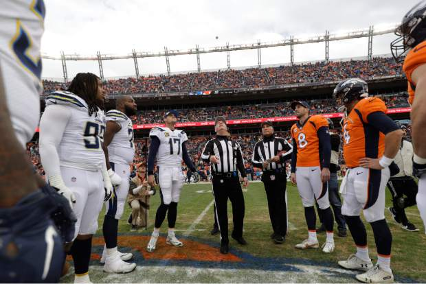 Referee John Parry (132) performs the coin toss during the first half of an NFL football game, Sunday, Dec. 30, 2018, in Denver. (AP Photo/Jack Dempsey)