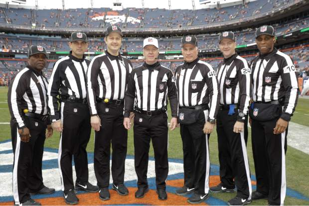 Officials pose before an NFL football game between the Los Angeles Chargers and the Denver Broncos, Sunday, Dec. 30, 2018, in Denver. They are, from right, line judge Julian Mapp (10), down judge David Olive, back judge Perry Paganelli (46), referee John Parry (132), umpire Mark Pellis, field judge Matt Edwards, line judge Julien Mapp, and side judge Michael Banks. (AP Photo/Jack Dempsey)