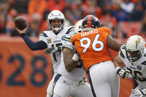 Los Angeles Chargers quarterback Philip Rivers throws a pass under pressure from Denver Broncos defensive end Shelby Harris (96) during the first half of an NFL football game, Sunday, Dec. 30, 2018, in Denver. (AP Photo/David Zalubowski)