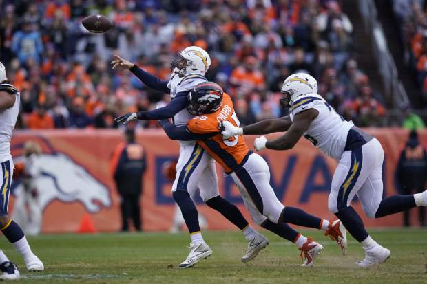Los Angeles Chargers quarterback Philip Rivers gets a pass off under pressure from Denver Broncos outside linebacker Bradley Chubb during the first half of an NFL football game, Sunday, Dec. 30, 2018, in Denver. (AP Photo/Jack Dempsey)