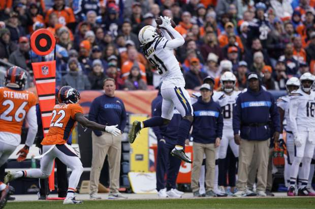 Los Angeles Chargers wide receiver Mike Williams (81) makes a catch as Denver Broncos defensive back Tramaine Brock defends during the first half of an NFL football game, Sunday, Dec. 30, 2018, in Denver. (AP Photo/Jack Dempsey)