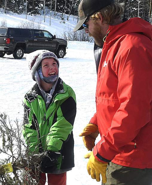 Jack Clifford, 9, is all smiles as he and his dad Damon prepare to load the family Christmas tree Sunday near Sunlight Mountain Resort.