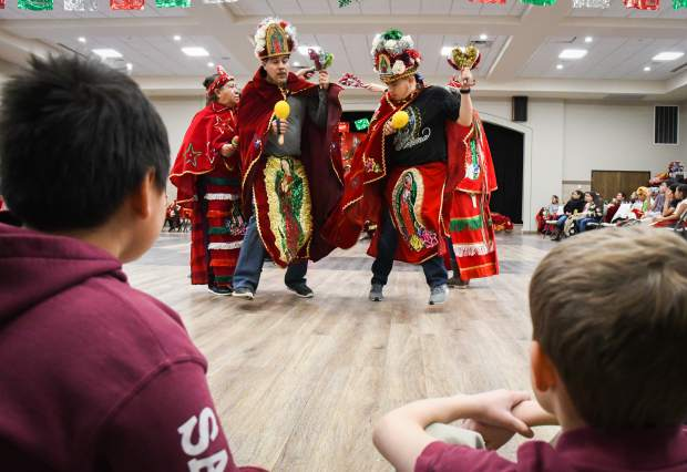 St. Stephen Catholic School students watch as Matachines perform a dance for the Our Lady of Guadalupe celebration held at the St. Stephen Catholic church on Wednesday.