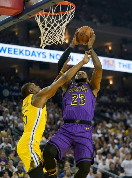 Los Angeles Lakers forward LeBron James (23) shoots over Golden State Warriors forward Kevin Durant (35) during the first half of an NBA basketball game Tuesday, Dec. 25, 2018, in Oakland, Calif. (AP Photo/Tony Avelar)