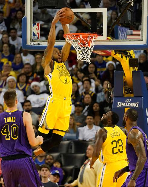Golden State Warriors guard Andre Iguodala (9) dunks in front of Los Angeles Lakers center Ivica Zubac (40) during the first half of an NBA basketball game Tuesday, Dec. 25, 2018, in Oakland, Calif. (AP Photo/Tony Avelar)