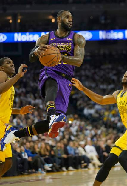 Los Angeles Lakers forward LeBron James (23) drives between Golden State Warriors' Kevon Looney (5) and Andre Iguodala during the first half of an NBA basketball game Tuesday, Dec. 25, 2018, in Oakland, Calif. (AP Photo/Tony Avelar)