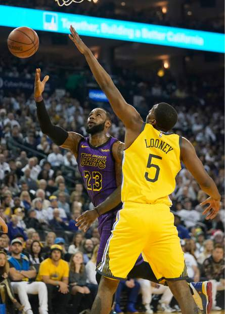 Los Angeles Lakers forward LeBron James (23) drives to the basket against Golden State Warriors forward Kevon Looney (5) during the first half of an NBA basketball game Tuesday, Dec. 25, 2018, in Oakland, Calif. (AP Photo/Tony Avelar)