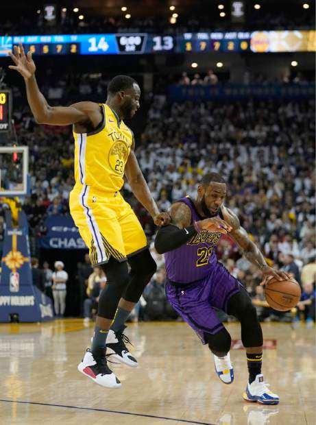 Golden State Warriors forward Draymond Green (23) fouls Los Angeles Lakers forward LeBron James (23) during the first half of an NBA basketball game Tuesday, Dec. 25, 2018, in Oakland, Calif. (AP Photo/Tony Avelar)