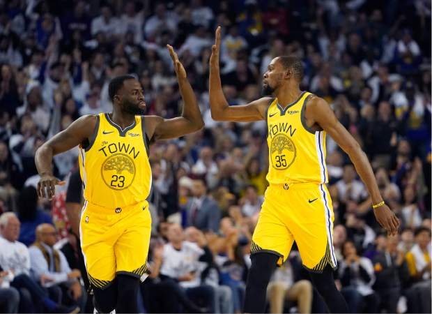 Golden State Warriors forward Draymond Green (23) high-fives Kevin Durant (35) after the latter's 3-point basket against the Los Angeles Lakers during the first half of an NBA basketball game Tuesday, Dec. 25, 2018, in Oakland, Calif. (AP Photo/Tony Avelar)
