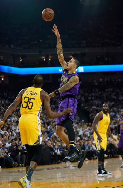 Los Angeles Lakers forward Kyle Kuzma (0) shoots over Golden State Warriors forward Kevin Durant (35) during the first half of an NBA basketball game Tuesday, Dec. 25, 2018, in Oakland, Calif. (AP Photo/Tony Avelar)
